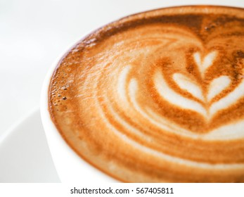 Close up white coffee cup with heart shape latte art on white table.