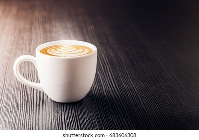 Close up white coffee cup with heart shape latte art foam on black wood table near window with light shade on tabletop at cafe.