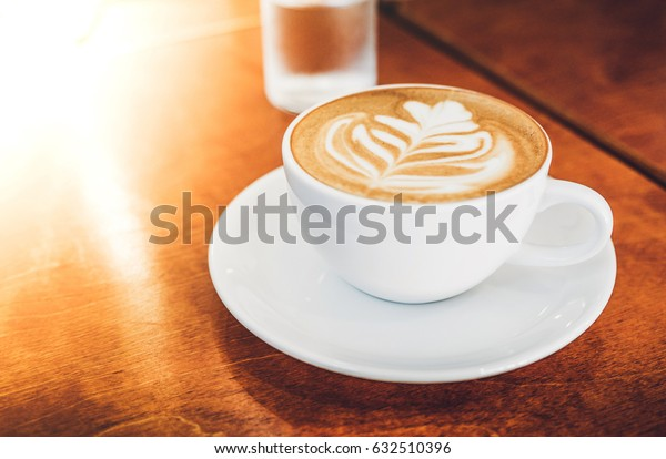 Close up white coffee cup with heart shape latte art on wood table at cafe near window light flare