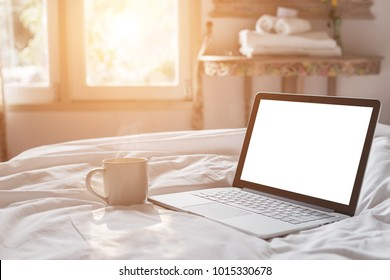 Close up white coffee cup and laptop on the bed in morning time with soft light from window, Focus on cup