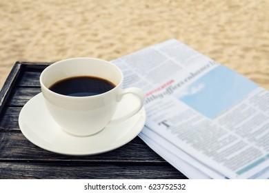 Close up white coffee cup on wood table at sunrise sand beach with newspaper in the morning, warm tone , Thailand