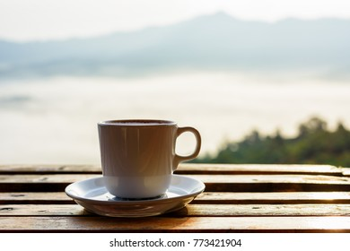 Close up white coffee cup on wood table and view of sunrise background