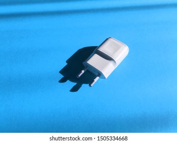 Close up to white color adapter plug on blue paper pastel on background. Technology background view. Usb wall charger plug isolated on a blue. Connector plug. Electrical adapter to USB port