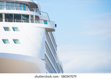 Close up of white cruise liner or ferry ship along facade of cabin windows, blue sky as copy space.