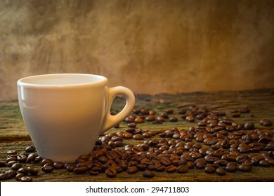 close up white cup of coffee and coffee beans on wood table and  old background still life style