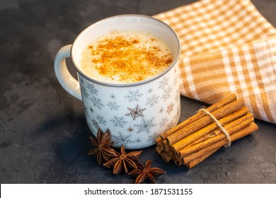 Close up white cup of salep milky hot drink of Turkey with cinnamon powder healthy spice on black wooden background (Sahlep - salep)
