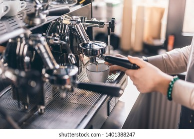 Close up of a white cup standing on the tray and barista pouring coffee from espresso machine