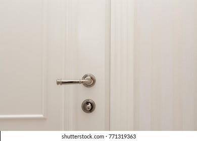 Close white door with metallic handle.