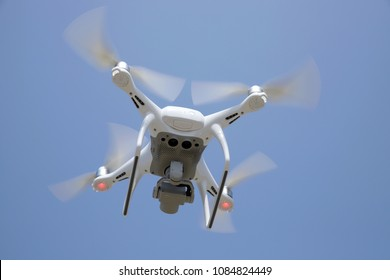 Close up of white drone flying in air and clear blue sky background