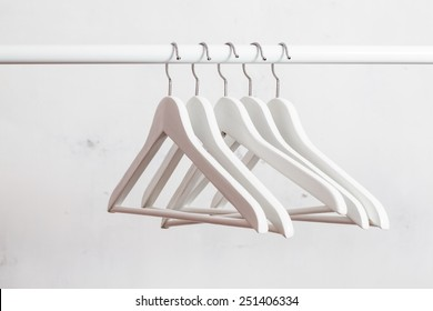 Close up of white empty hangers on background of white wall. Soft focus.