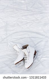 close up of white figure skates over ice background with marks from skating or hockey