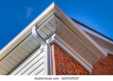 Close up of white frame gutter guard system, eaves through, fascia, drip edge, colonial white soffit with ventilation, brick facade siding on a luxury American single family home neighborhood USA