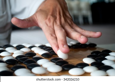 Close up white Go player hand showing how to hold and place the piece on crowded board. Selected focus.