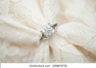 Close up of white gold and diamond engagement ring on an ivory lace wedding dress