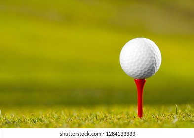 Close up of white golf ball on red tee on grass.