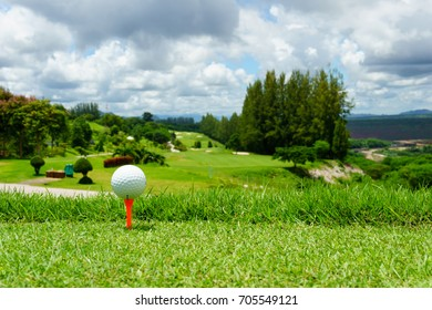 close up of white golf ball on orange tee on green grass with blue sky and cloud and view of mountain background in sunny day. copy space for your text.