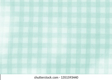 Close up of white and green checked fabric tablecloth texture background.