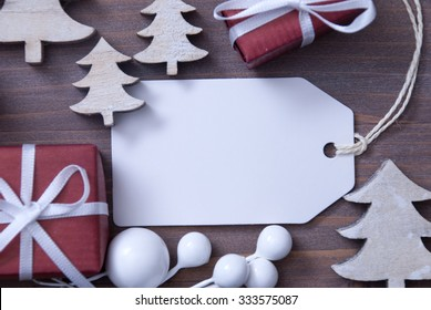 Close Up Of White Label With Ribbon, Red Christmas Gift Or Present, Ribbon And Christmas Tree. Christmas Decoration Or Card On Wooden Background. Copy Space Or Free Text For Advertisement.