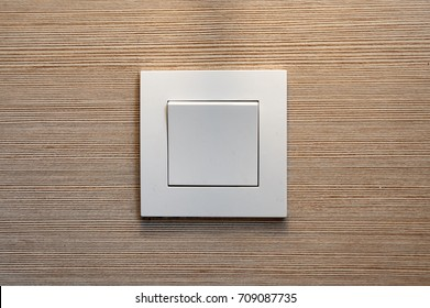 Close up white light switch with wooden texture background. Copy space.