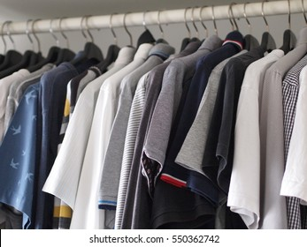 Close up of white modern men wardrobe with variety casual shirt on black hanger.