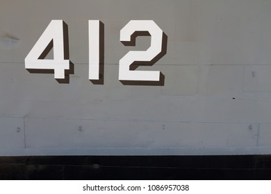 Close up The White number on grey metal background of Decommission navy warship or old battle ship for Memorial and Education parked on the ground. Have copy space.