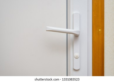 Close up white plastic door handle on white door