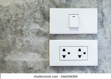 Close up of a white plastic light switch turned on and white 2 power sockets on concrete wall, loft interior style room.