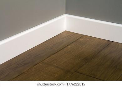 Close up of white plastic plinths on dark wooden oak floor parquet.