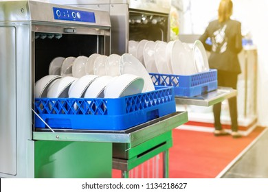 close up white plate on basket in automatic dishwasher machine for industrial