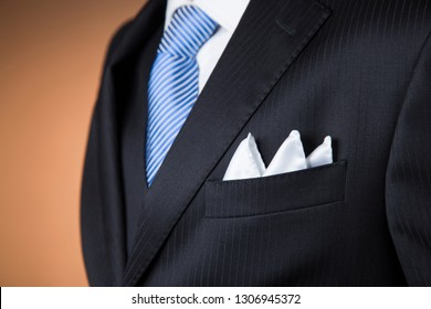 close up of a white pocket handkerchief folded with three points in the pocket of a black pinstripe suit with a blue tie and orange background