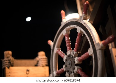 Close up of white and red painted historic antique sailing ship steering wheel mounted with rope wrapped wood log pillar in background at night
