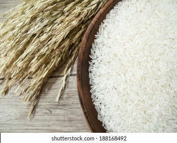 Close up white rice on the wooden plate and rice plant ,  uncooked raw cereals