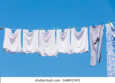 close up of white shirts hanging for dry with the sun background with blue clear sky in summer season.
