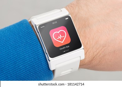 Close up white smart watch with health app icon on the screen is on hand