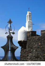 close up of the white tower of the historic fortress in puerto de la cruz in tenerife with church bell tower and weather vane in the foreground in bright sunlight
