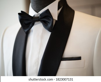 Close up of White tuxedo jacket suit with big black bow and black handkerchief