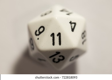 Close up of a white twenty-sided die, top-down view, with the number eleven showing.