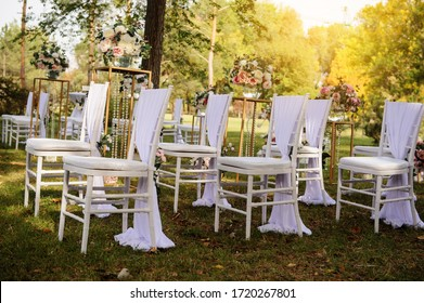 Close up white vintage chairs decorated with white and pink flowers roses and peony preparation for a wedding ceremony outdoor in the park/ forest.
