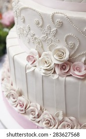 Close up white wedding cake decorate with roses and pearl