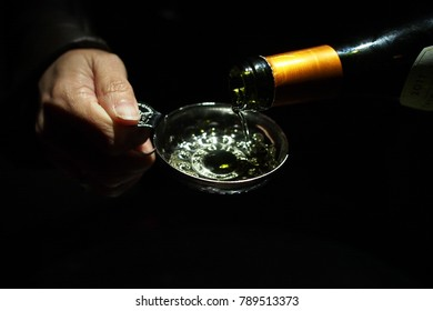 Close up of white wine testing; woman hand holds silver wine testing with another hand pours white white into the cup