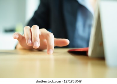 Close up of a white woman's hand that anxiously taps her desk with her fingers while working on a laptop at the office. Concept for anxiety, stress, boredom, impatience and nervousness related to work