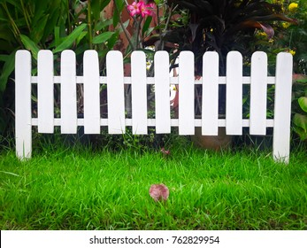 Close up white wood fence isolated on green grass.