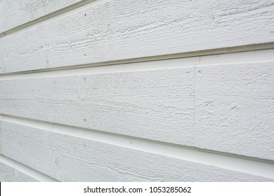 Close up of white wooden panel wall from side, shallow depth of field.