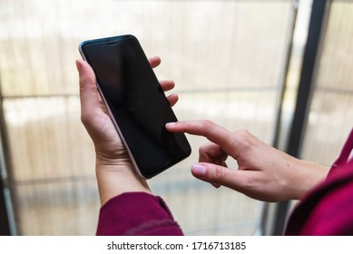 Close up of an white young woman at home, using her mobile phone. Copy space.