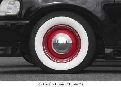 Close up of a Whitewall tyre with red trim and a silver, reflective hubcap/Whitewall Tires/Close on Whitewall tires with red trim.