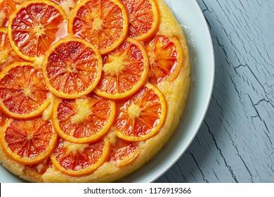 Close Up of Whole Blood Orange Ricotta Cornmeal Cake on Plate on Aqua Table