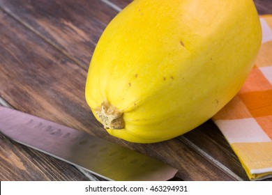 Close up of whole spaghetti squash on a wooden background.