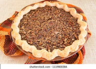 Close up of a whole Thanksgiving pecan pie on beige background