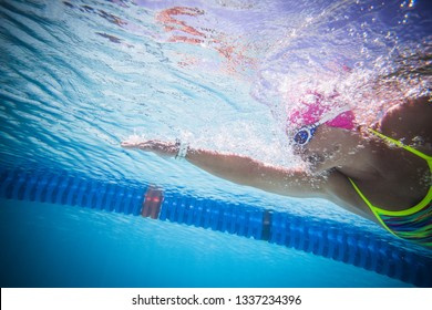 Close up wide angle photo of a female swimmer underwater in a swimming pool