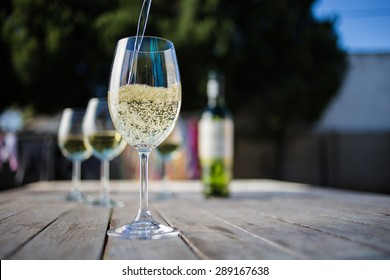 Close up wide angle  shot of a glass of white whine on a rustic table outside with natural light